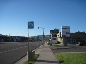 Super wide street, bus stop, foothills, clear dry Western light, US 89 sign...